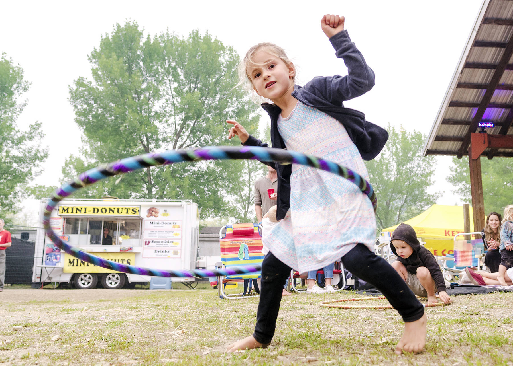 Yeva Mae Gidney gets the hang of a hula hoop over at the Barn Stage at Roots and Blues Saturday, Aug. 18. (Lachlan Labere/Salmon Arm Observer)