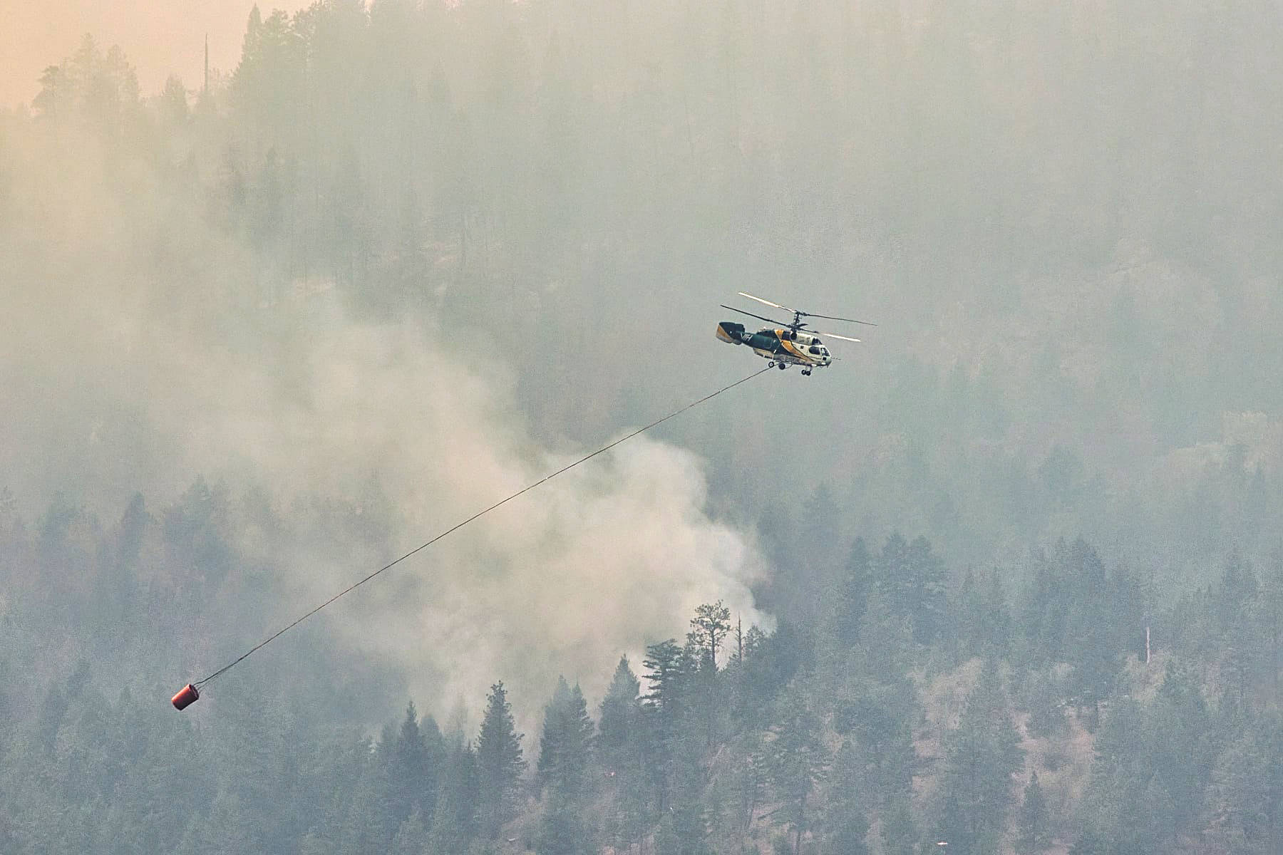 A helicopter buckets water over the White Rock Lake wildfire near Westside on Aug. 10. (Darren Wolf photo)